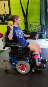Kaylan In Wheelchair Throwing Ball as Part of Physical Therapy