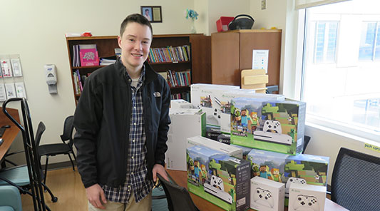 boy stands in front of xbox systems