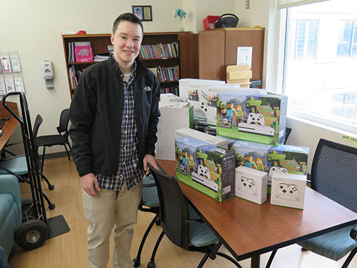 Boy stands in front of stack of xbox one systems