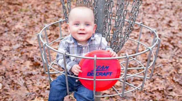 baby sitting in disc golf basket