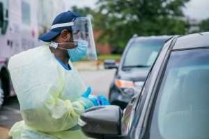 Healthcare worker in PPE talks to a patient at a drive-thru testing site.